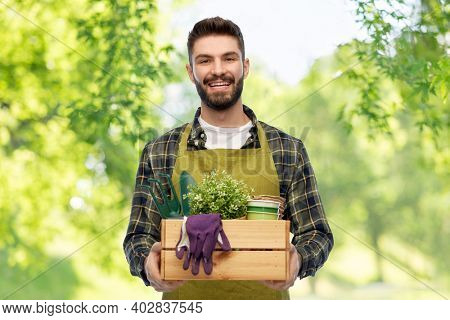 gardening, farming and people concept - happy smiling male gardener or farmer in apron with box of garden tools over green natural background