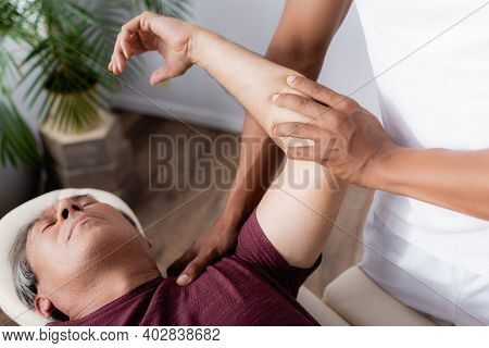 African American Chiropractor Correcting Arm Of Man On Massage Table