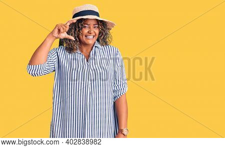 Young african american plus size woman wearing summer hat smiling and confident gesturing with hand doing small size sign with fingers looking and the camera. measure concept.