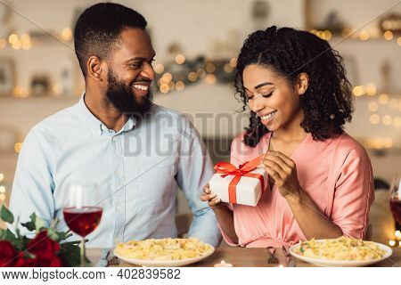 Portrait Of Smiling African American Woman Unwrapping Present From Her Handsome Boyfriend Or Husband