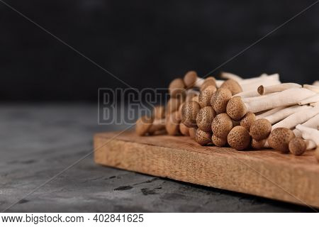 Group Of Brown Edible Mushrooms Native To East Asia Called 'buna Shimeji' On Wooden Cutting Board In