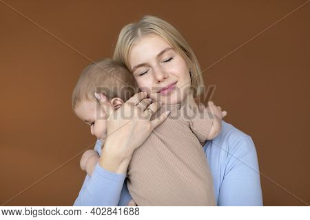 Happy Motherhood Concept. Loving Young Mother Blonde Woman Cuddling With Her Cute Little Baby, Brown