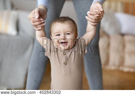 Happy Little Baby Boy Taking First Steps With Mother Help, Home Interior, Close Up. Laughing Cute To