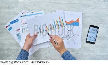 Businessman Checking Reported Profits On Paper.  Paperwork And Financial Concept. Close Up