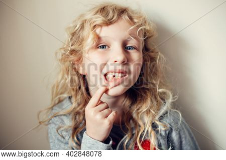 Cute Caucasian Blonde Girl Showing Her Missing Tooth In Mouth. Proud Child Kid Showing Lost Tooth An
