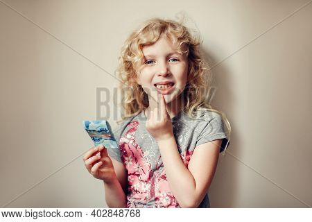 Caucasian Blonde Girl Showing Her Missing Tooth In Mouth And Holding Money From Tooth Fairy. Proud C