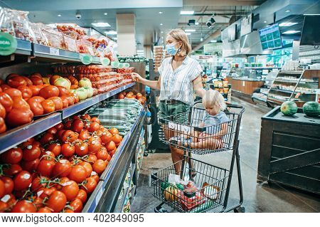 Grocery Shopping With Kids. Young Mother In Protective Face Mask Buying Food With Kid Baby In Shoppi