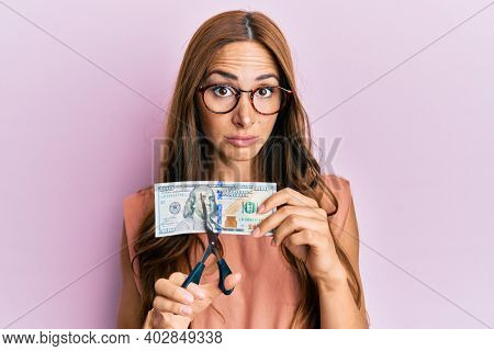 Young brunette woman cutting dollars with scissors for currency devaluation skeptic and nervous, frowning upset because of problem. negative person.