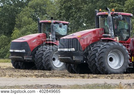 Two Red Tractors, Work In The Field On A Large Tractor, Harvesting, Farming. Two Red Tractors In A F