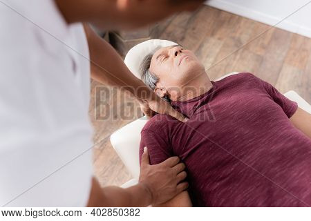 Blurred African American Chiropractor Massaging Arm Of Mature Man On Massage Table