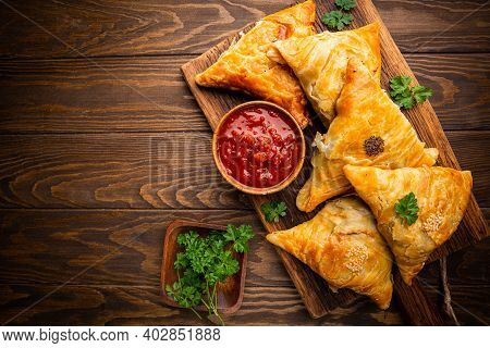 Samsa Or Samosas With Meat And Vegetables With Tomato Sauce On Wooden Background. Traditional Asian