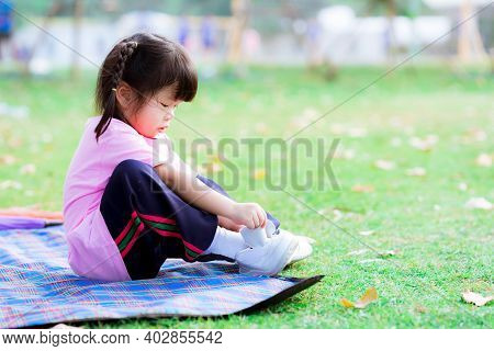 Active Cute Girl Is Trying To Wear Sneakers For Sport On The Lawn. Kids Practice Basic Daily Routine