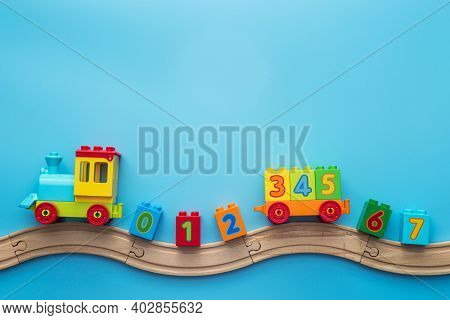 Colorful Toy Train Locomotive With Numbers On Wooden Railway On Blue Background. Kids Toys Backgroun