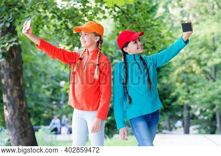 Happy Little Girls Make Video Call With Modern Mobile Phones In Park, Video Conferencing.