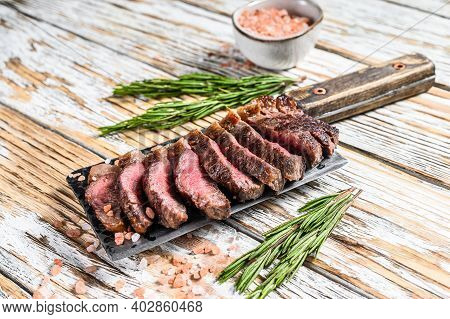 Grilled Top Sirloin Cap Or Picanha Steak On A Meat Cleaver With Herbs. White Wooden Background. Top