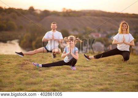 Happy Healthy Active Family Of Three Do Gymnastic Exercises Together Outdoor At Sunset. Focus On Lit