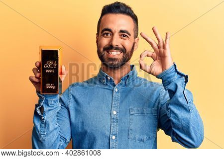 Young hispanic man holding gold ingot doing ok sign with fingers, smiling friendly gesturing excellent symbol