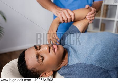 Chiropractor Working With Injured Arm Of Young African American Patient On Massage Table