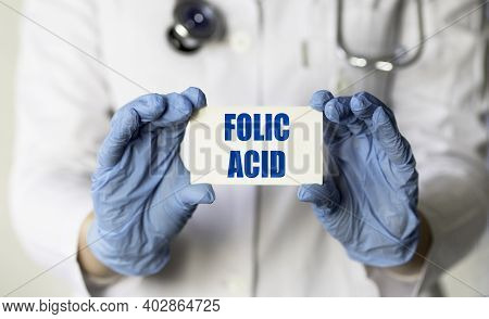 A Medical Worker In Gloves Holds A Card With The Words Folic Acid. Medical Concept.