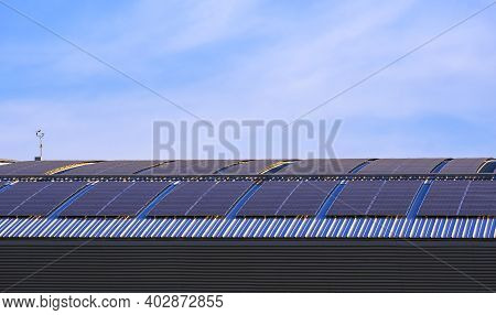 Many Solar Panels On Curved Steel Roof Of Industrial Building Against Blue Sky Background