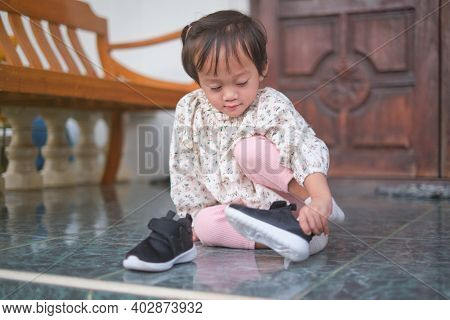 Cute Little Asian 2 Year Old Toddler Girl Sitting And Concentrate On Putting On Her Black Shoes, Sne