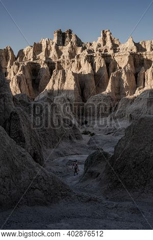 Woman Walks Between Hoodoos In Badlands National Park