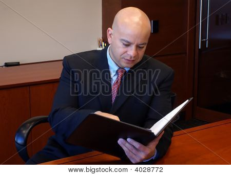 Man Is Suit Reading Documents Inside Office.