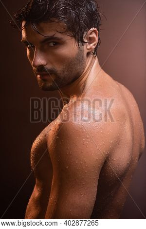 Sexy, Wet, Muscular Man Looking At Camera On Dark Background