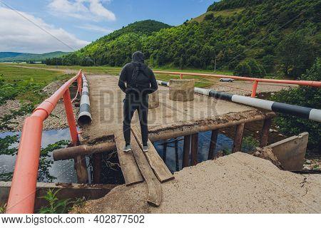 Businessman Rebuilding A Broken Bridge. A Man Crosses A Broken Bridge.