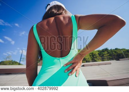 Back Pain. Athletic Woman In Pink Sportswear Standing At The Seaside Rubbing The Muscles Of Her Lowe