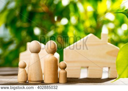 Wooden Toy House And Wooden Family On Foliage Background