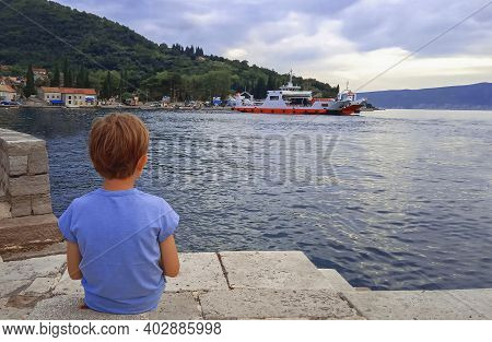 An Unrecognizible Caucasion Boy Is Sitting At Coast And Watching For Ferry-boats.