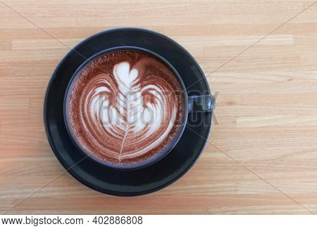 Top View Of Hot Organic Cocoa With Foam Froth Art In Black Ceramic Cup On Wooden Table In Cafe