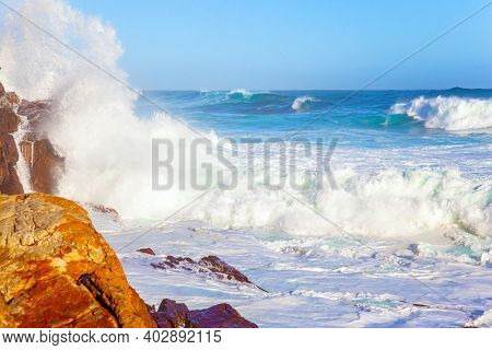 White foam of the ocean surf. Powerful ocean surf. South Africa. Cape of Good Hope at the southern tip of the Cape Peninsula. Bright sunny summer february day
