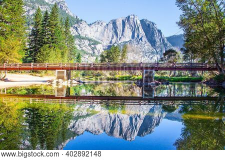 The Yosemite Valley. The rock-monolith El Capitan and the bridge is reflected in the smooth water. Yosemite Park is located on the slopes of the Sierra Nevada