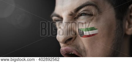 A Screaming Man With The Image Of The Kuwait National Flag On His Face