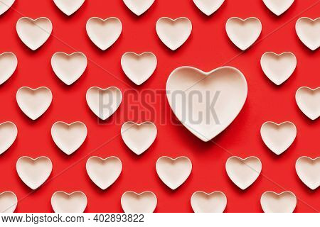 Pattern With Voluminous Reduced-pink Hearts On A Red Background. A Seamless Pattern. One Heart Is Bi