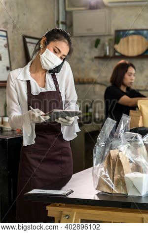 Asian waitress take order from mobile phone for takeout and curbside pickup orders while city lockdown. They wear protective face mask to prevent from infection of coronavirus COVID-19 pandemic.
