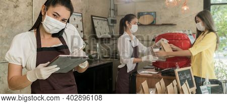 Panoramic Asian waitress take order from mobile phone for takeout or curbside pickup orders while city lockdown. They wear face mask to prevent from infection of coronavirus COVID-19 pandemic.