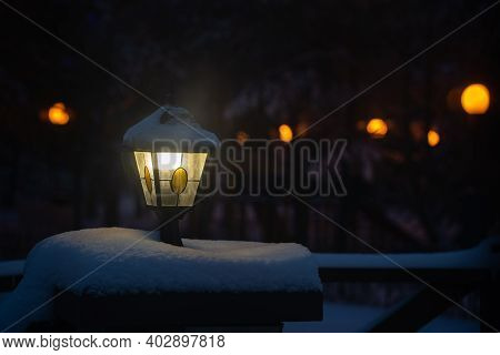 Winter Night View - A Burning Vintage Street Lantern On A Snow-covered Pedestal Against The Backgrou