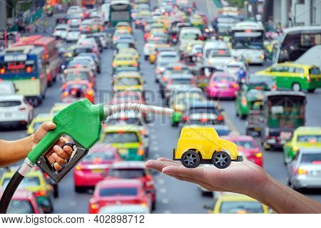 Left Hands Of Men Who Were Holding An Automatic Nozzle To Make Refill Oil On Yellow Toy Car On Right