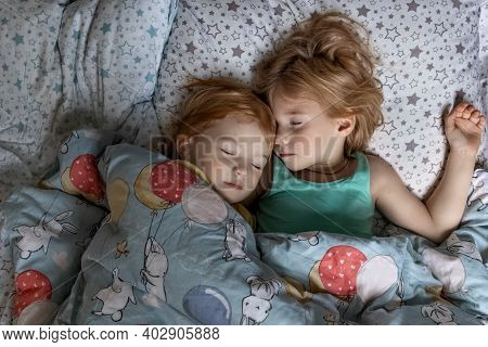 Two Little Sibling Girls Sisters Sleeping In An Embrace In Bed Under One Blanket.