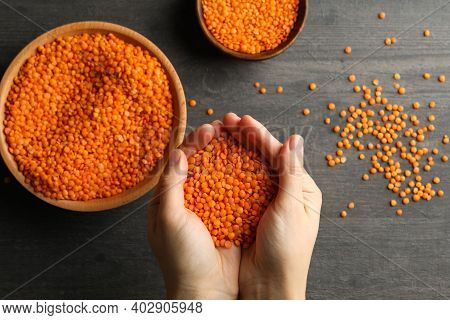 Female Hands Holds Red Legumes Over A Dark Background With Bowls Of Legumes
