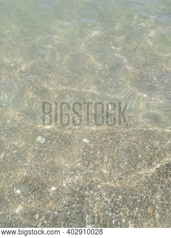 Shoreline With Small Pebbles And Water Close-up. High Quality Photo