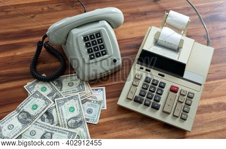 Old Fashioned Calculator, Telephone And Dollars On Desk