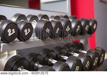 Dumbbells Of Different Weights With Numbers Are On A Rack In The Gym. Sports Equipment, Training, Bo