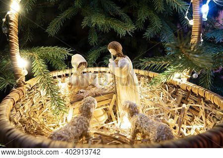 Baby Jesus Resting On A Manger With Light From The Star