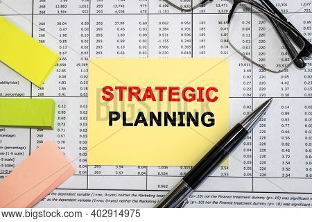 Strategic Planning Is Written On A Yellow Sheet That Lies On A Document With Columns Of Numbers Near