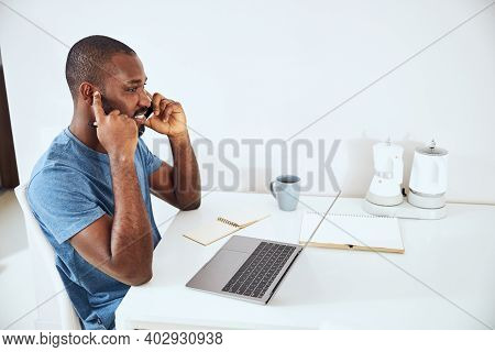 Mixed-race Male Plugging His Ear During A Phone Talk