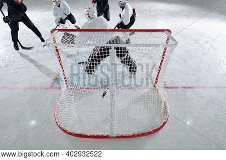 Back view of hockey player in sports uniform and protective helmet standing in the net in front of group of rivals attacking puck during play